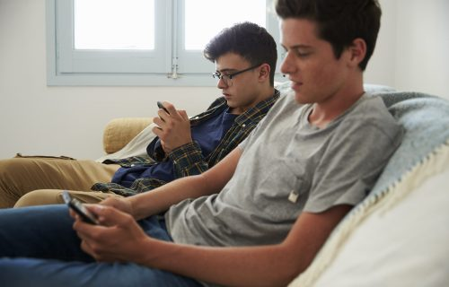 Teenage boys sitting on a couch using smartphones